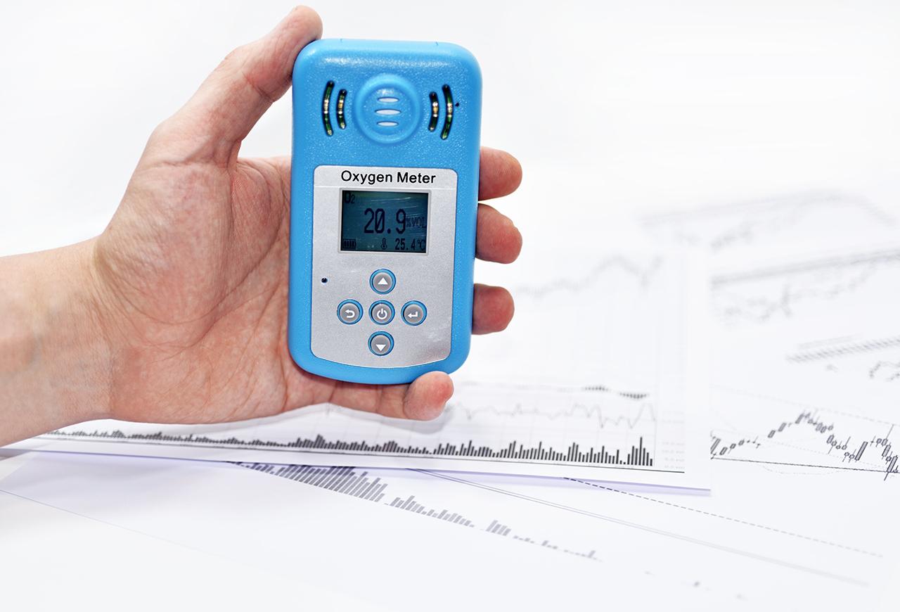 Una mano sostiene un medidor de ozono en aire sobre un plano